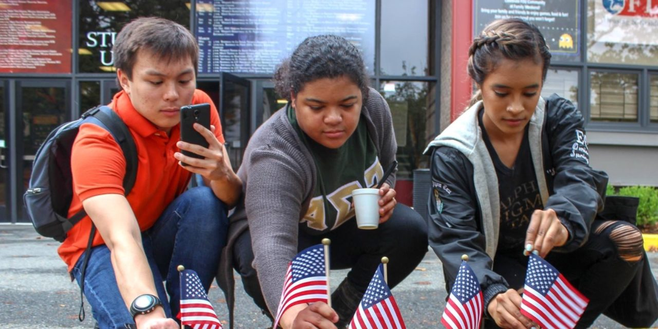 Students stick small American flags in the ground.