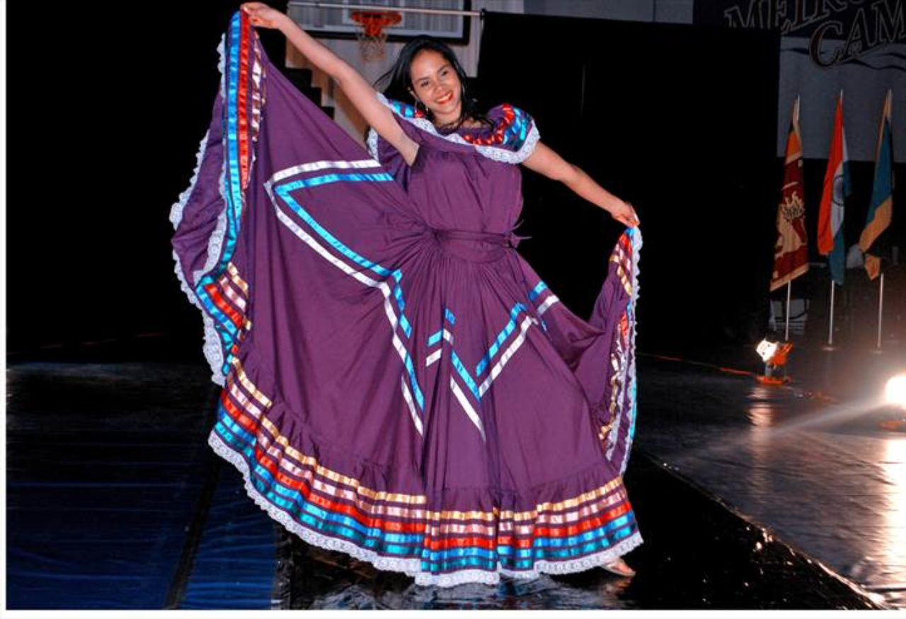 photo of an international student on stage wearing a cultural dress