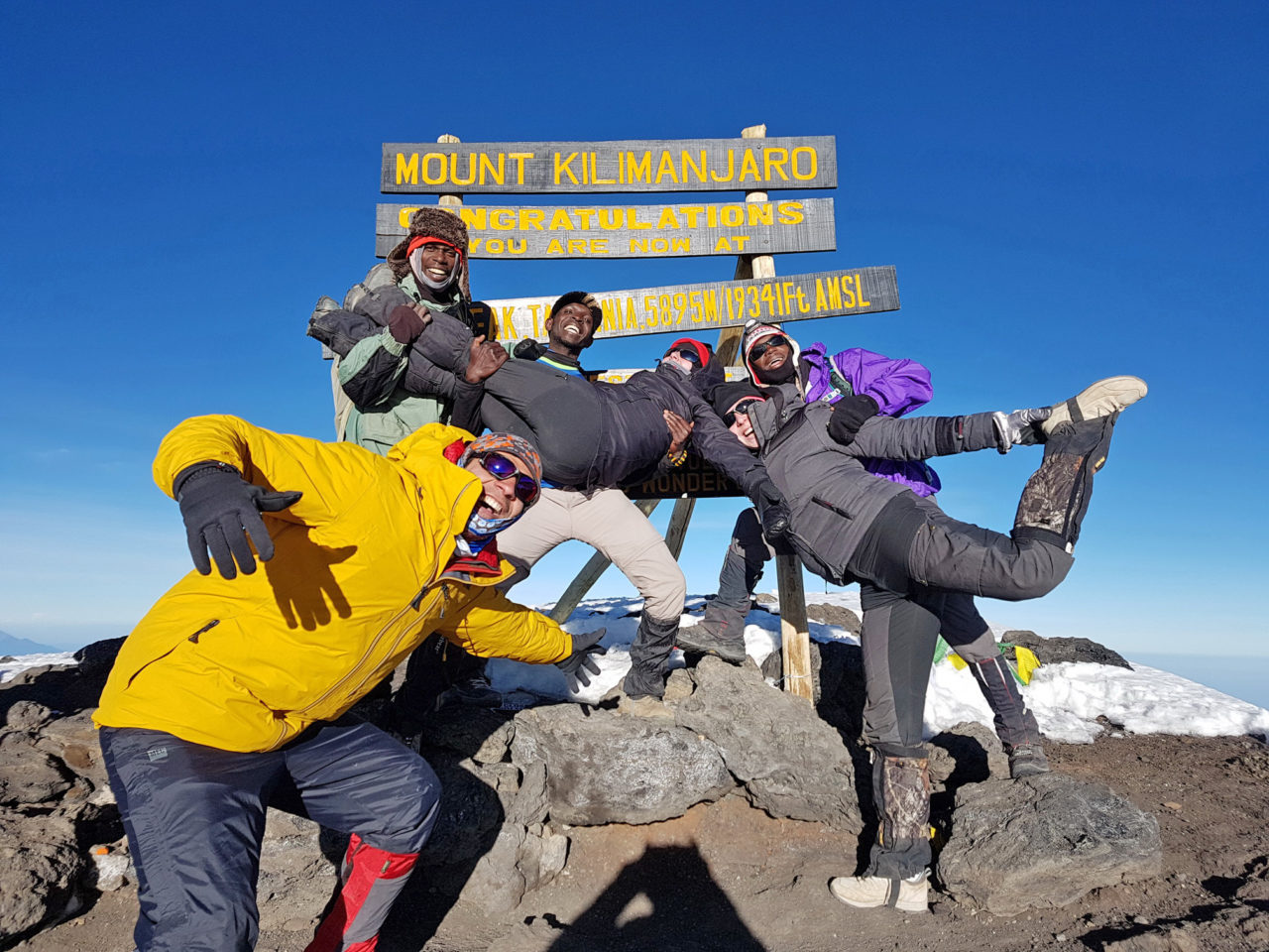 Foad Davani, BA'13, MAS'14 (Van), and his climbing guides and crew celebrate reaching the top of Mount Kilimanjaro