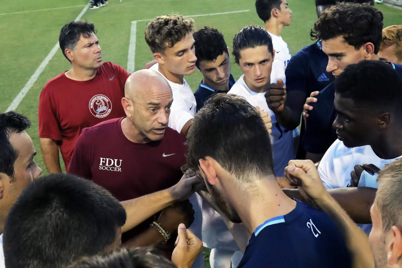 Men's soccer head coach Seth Roland talks to his team.