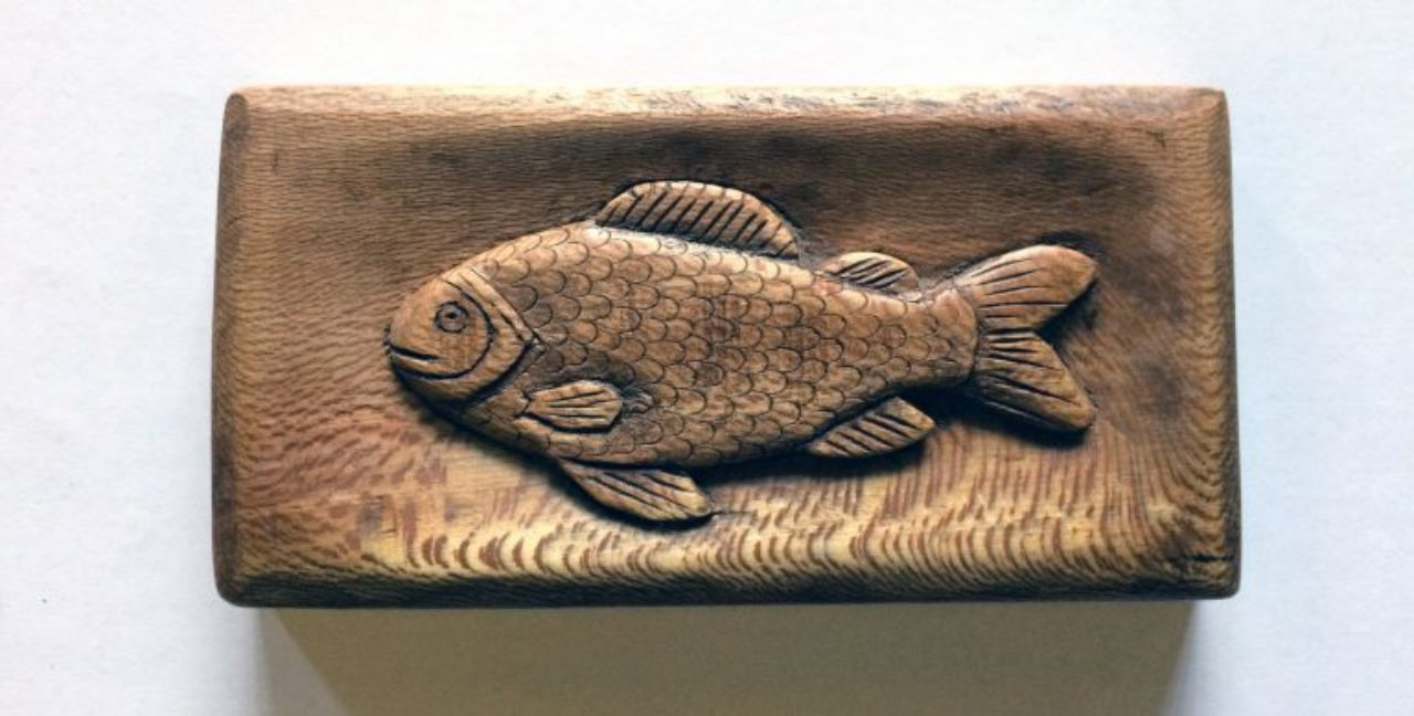 Wroxton College groundskeeper Robert Denton spends his free time making wood carvings, like this fish, and ornate walking sticks.