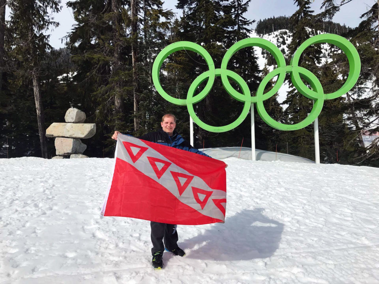 Orsini holding the flag of his fraternity, Tau Kappa Epsilon, in front of the Olympic Rings on Cypress Mountain in British Columbia, Canada.