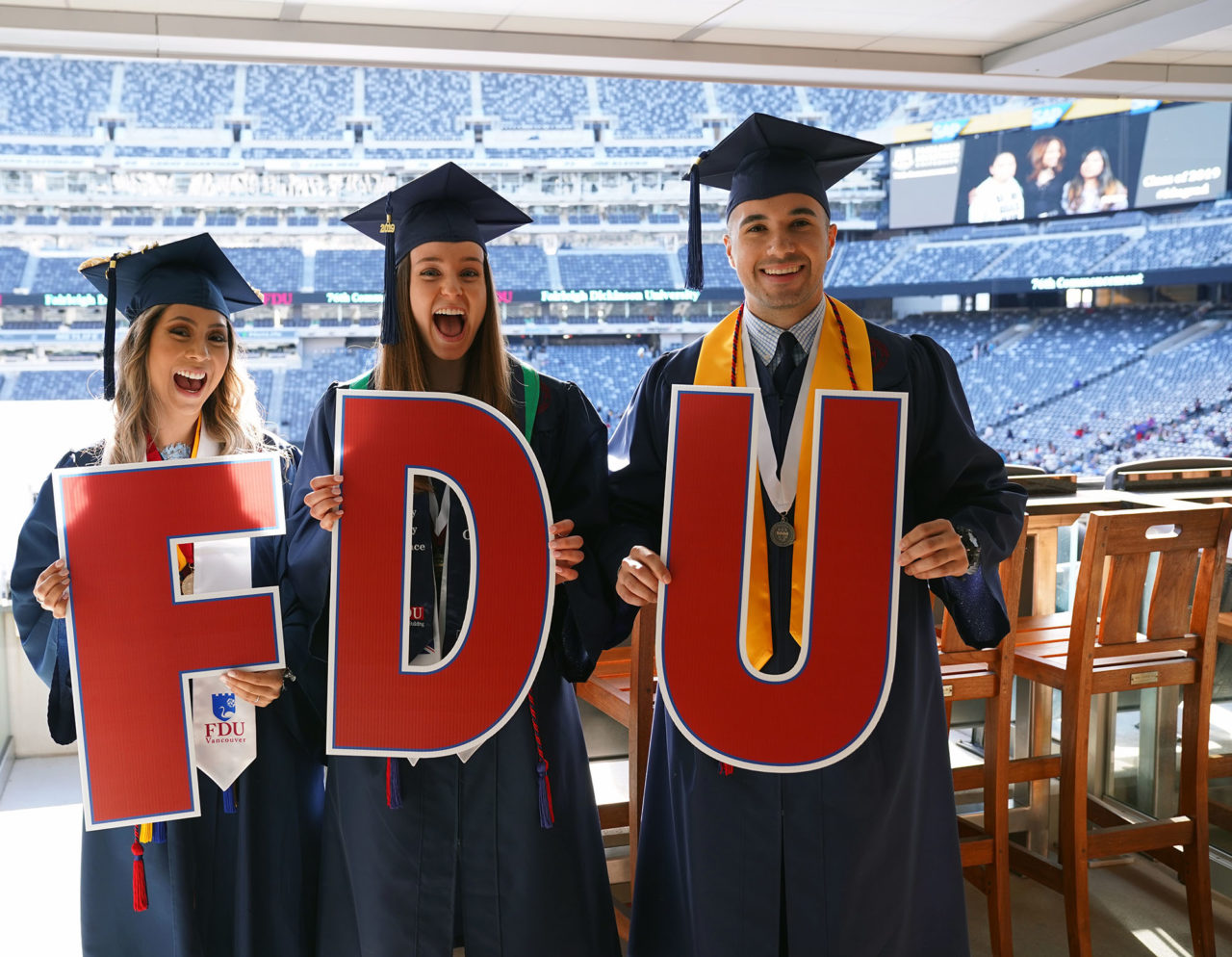 three graduates holding FDU sign