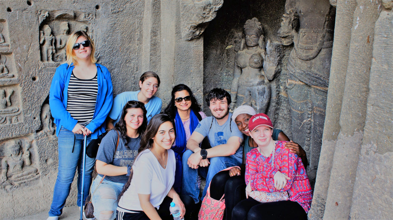 Students and Professor Kiron Sharma (center with blue scarf) gather around with caves as the backdrop.