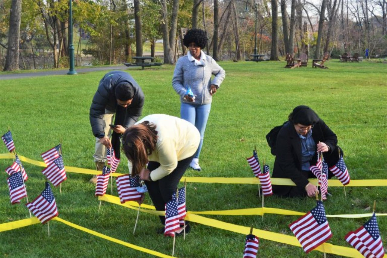 Metropolitan Campus Veterans Day ceremony attendees plant flags to honor veterans.