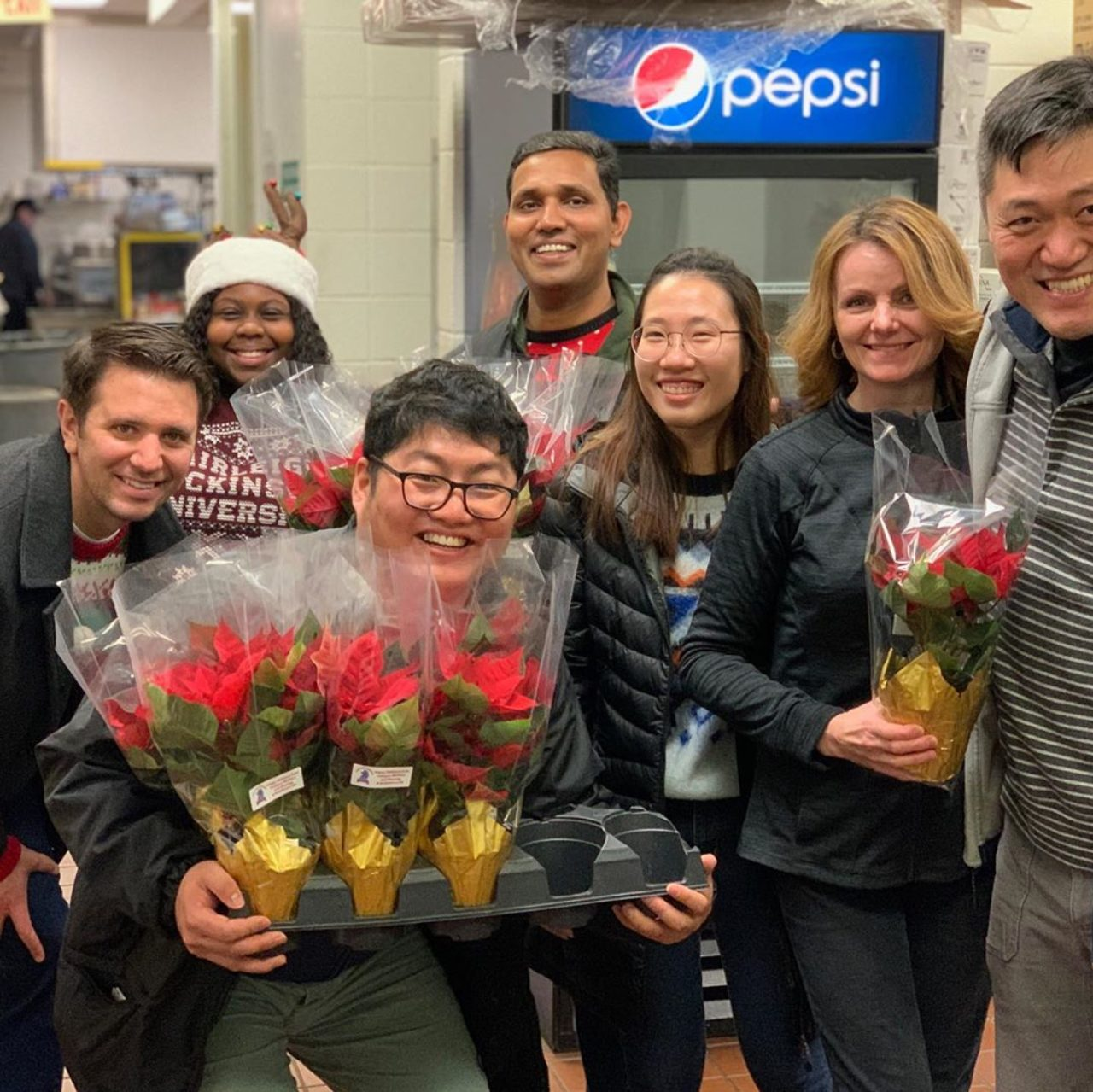 A group of students pose for a photo while holding poinsettias.