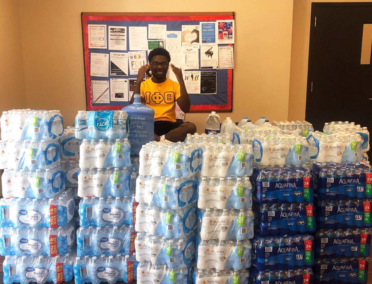 A student sits in front of mountains of bottled water cases.