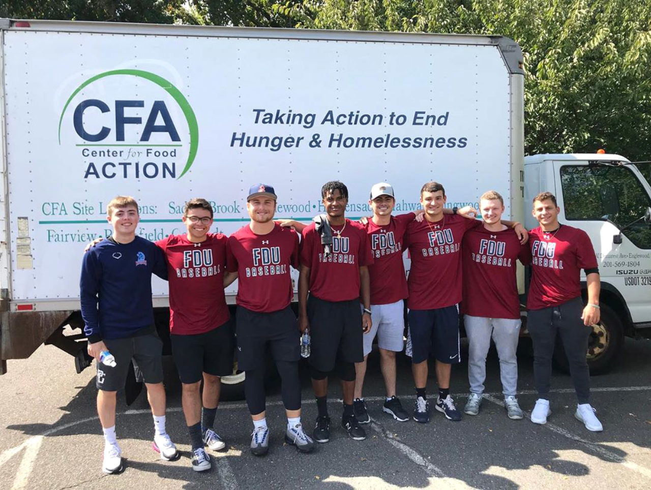 """Knights baseball players pose in front of a truck that reads, """"CFA Center for Food Action. Taking Action to End Hunger & Homelessness."""""""