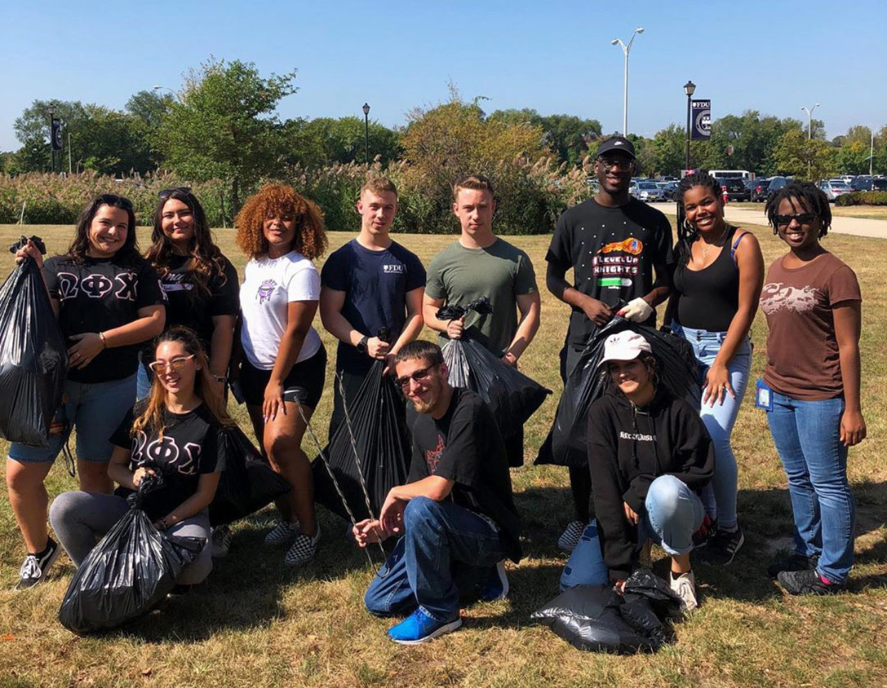 A group of students holding garbage bags pose for a photo.