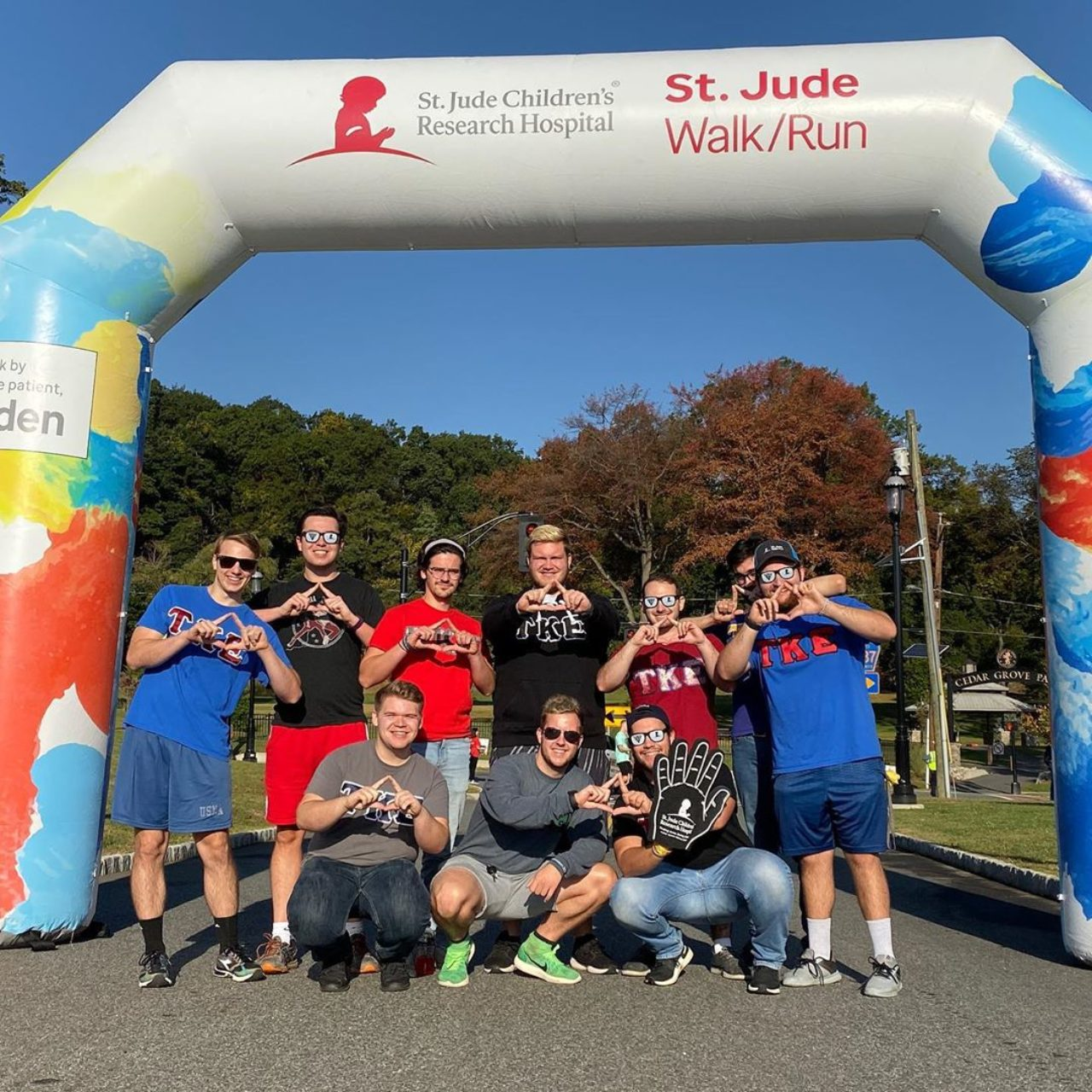 """Tau Kappa Epsilon members pose in front of an inflatable arch that reads, """"St. Jude Children's Research Hospital. St. Jude Walk/Run"""