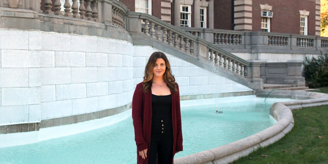 Kaity stands in front of a fountain behind Hennessy Hall at FDU's Florham Campus.