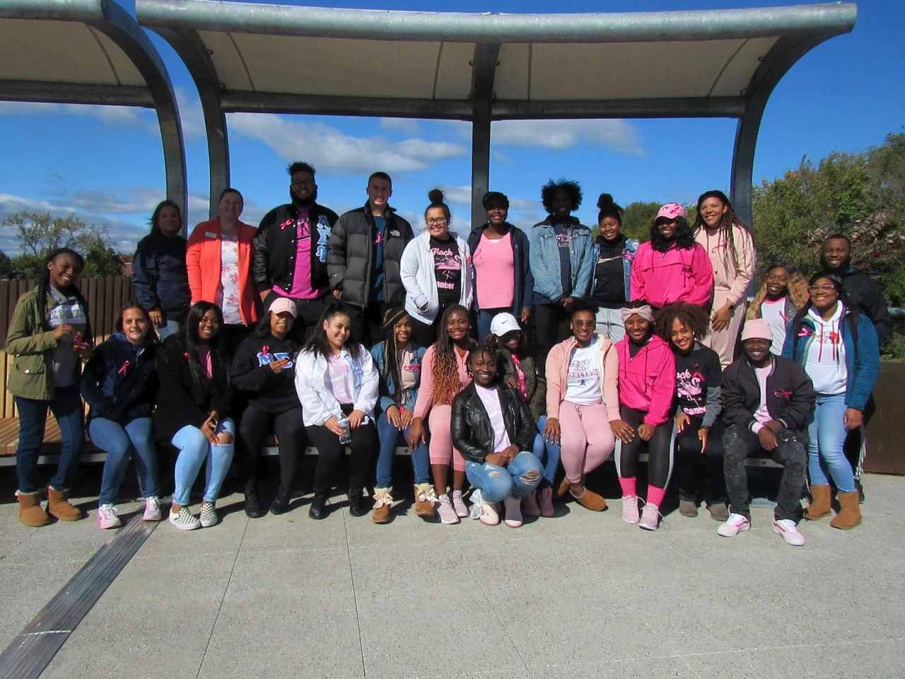 A group of students in pink clothes pose for a photo on the Metro Campus footbridge.