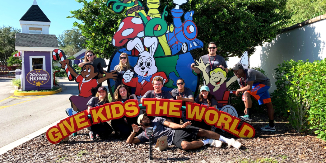 """A group of students pose in front of a sign that reads """"Gives Kids the World."""""""