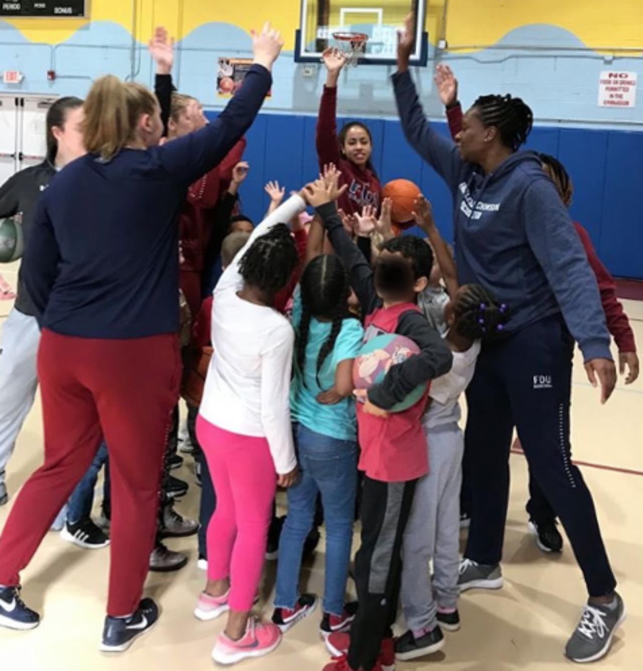 Knights women's basketball members high five children