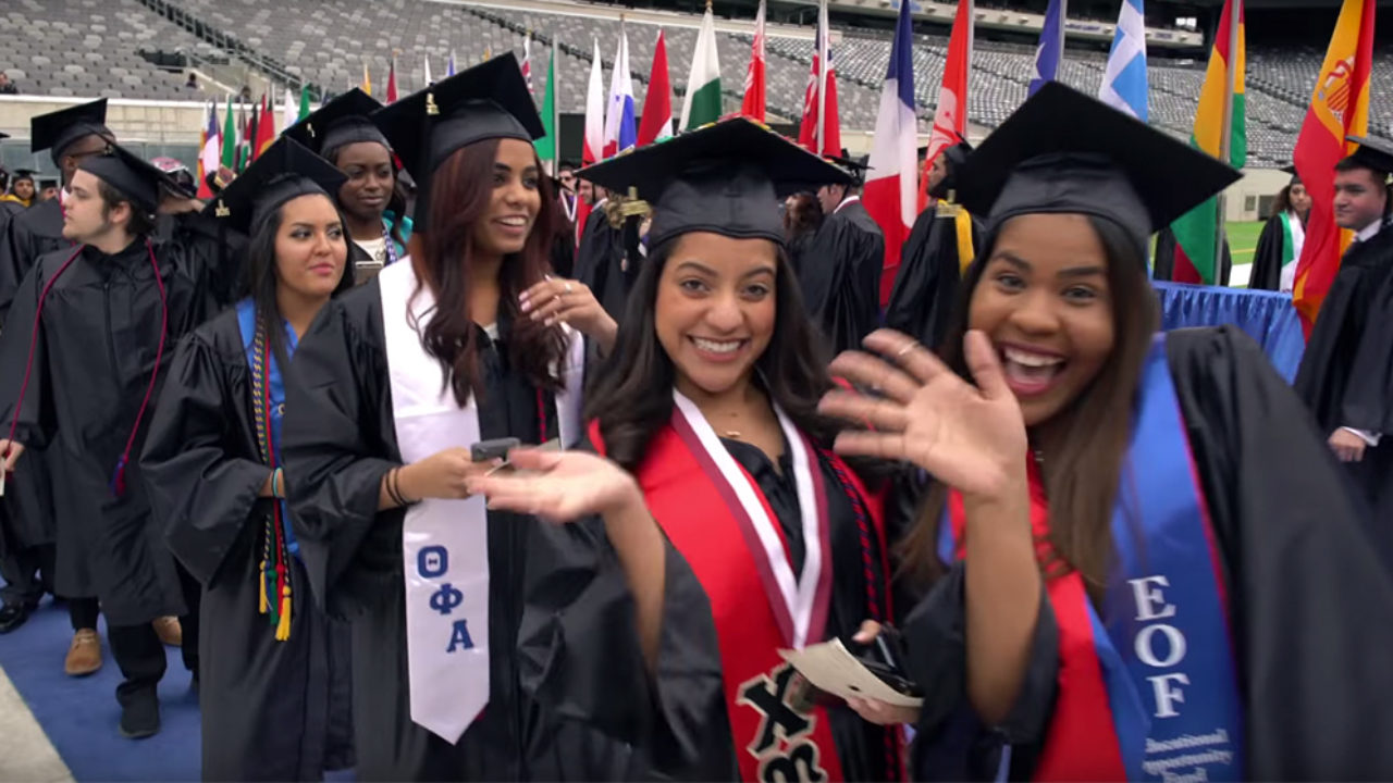 Students smile at wave in cap and gowns at graduation