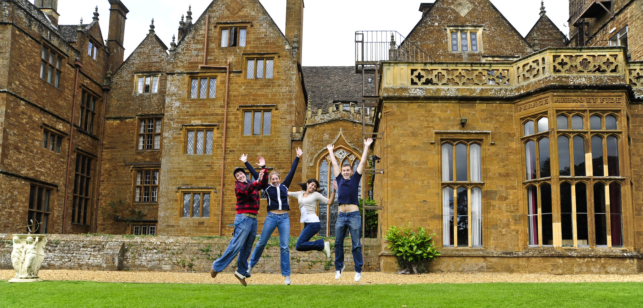 Wroxton Abbey in the background, with students jumping joy in the foreground.