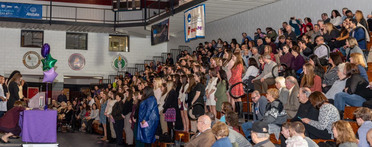 A crowd of students and their families stands in the bleachers facing the stage.