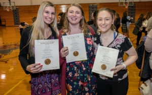 Three female students stand side by side and hold their Kappa Delta Pi certificates.