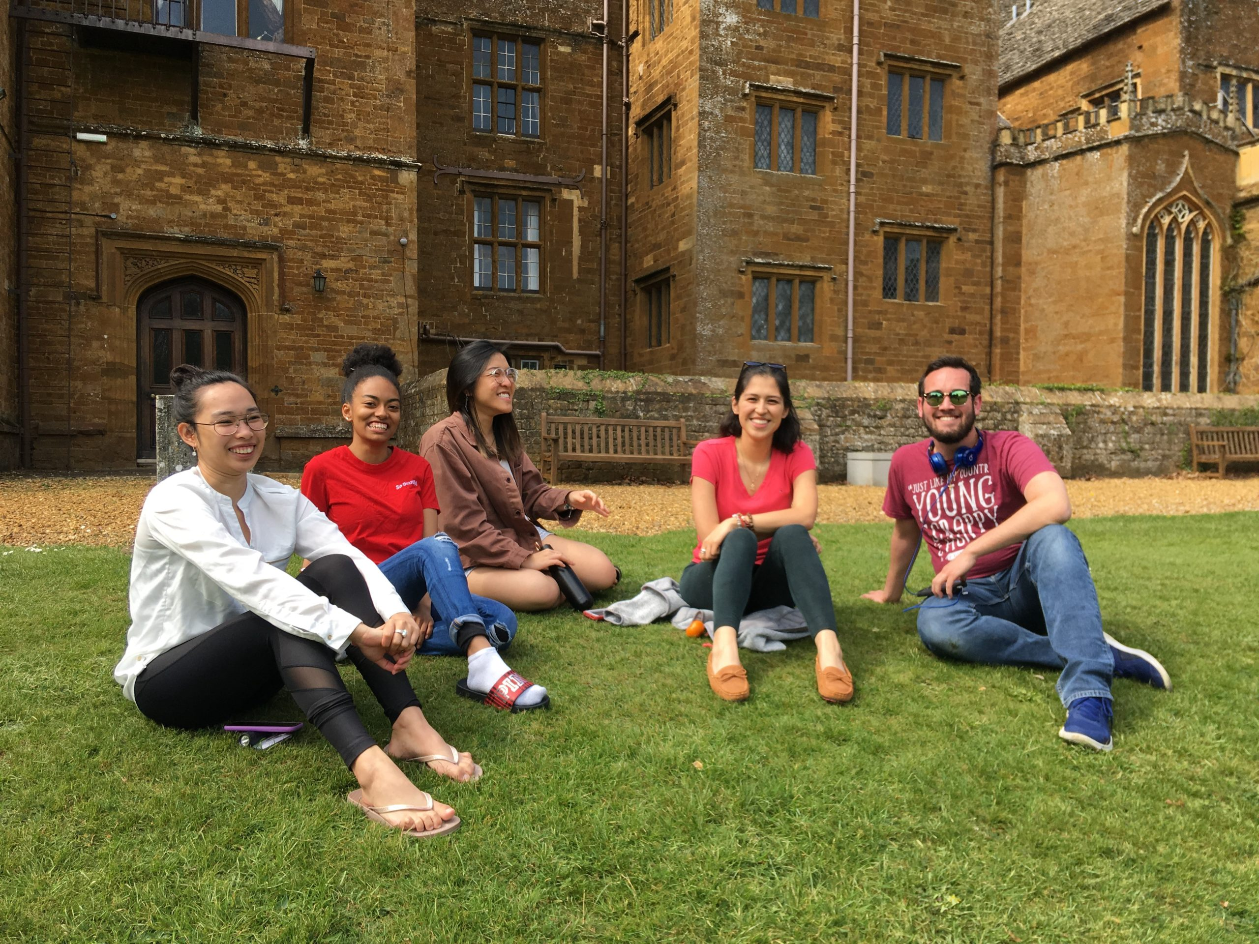 Students sit and smile in front of the Wroxton Abbey