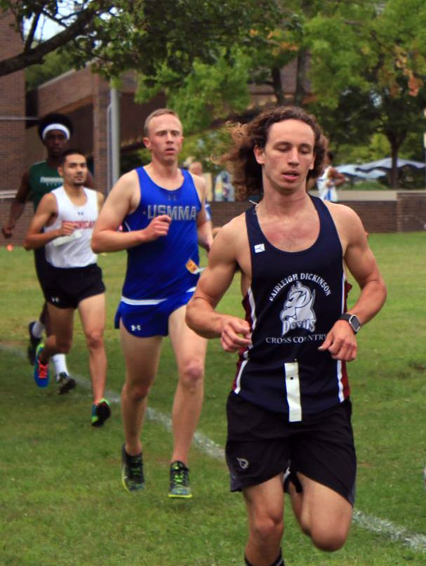 """Duerr runs in a cross country race wearing a jersey that reads """"Fairleigh Dickinson Cross Country"""""""