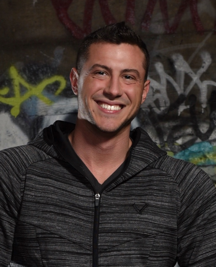 A male in a dark grey hooded sweatshirt smiles at the camera.