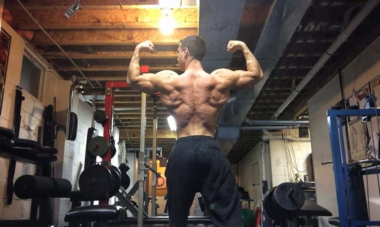 Male bodybuilder stands and faces away from the camera, with arms flexing at ninety degree angles from his torso.