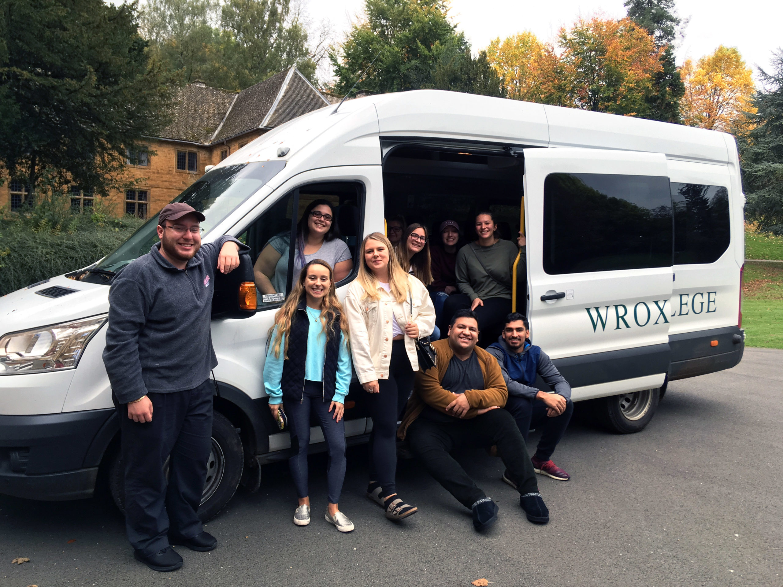 "Students in a mini van that reads ""Wroxton College."""