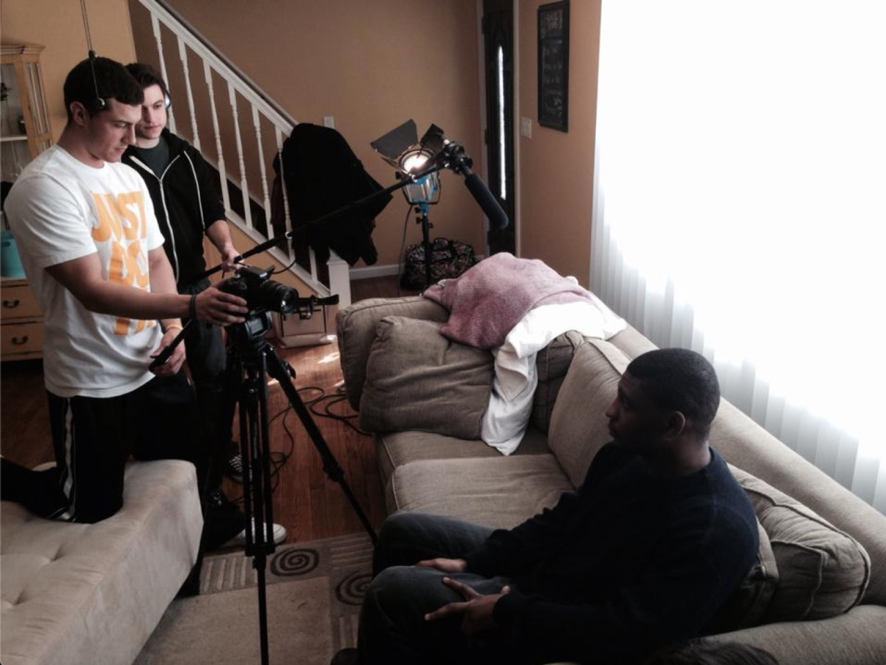 Two males stand behind a camera and a boom microphone as a third male sits on a sofa to their right.