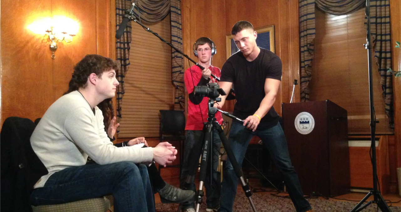 A male sits on a chair facing right while two other males stand and position a boom microphone and a camera for filming.