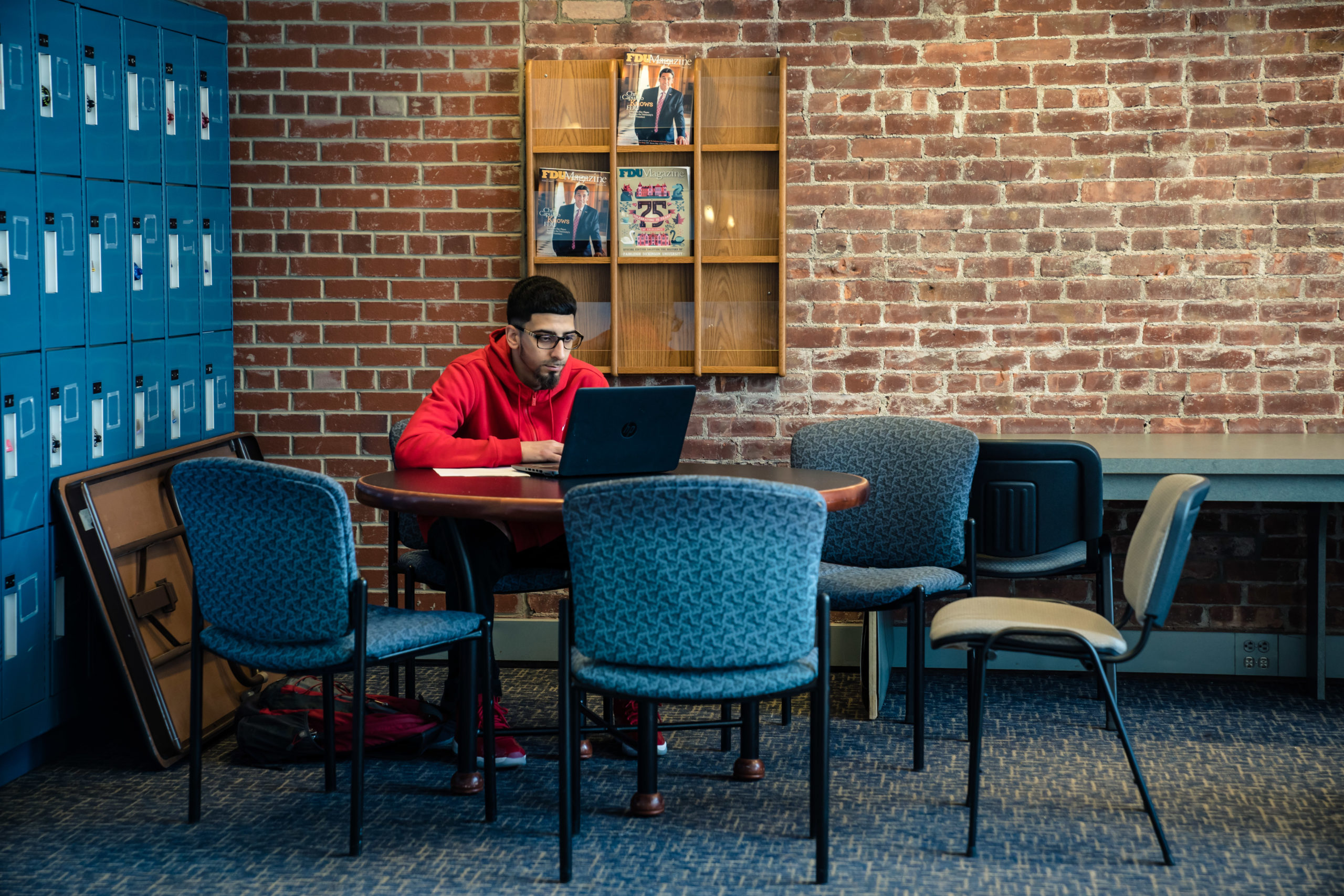 A student works on a laptop at an empty table