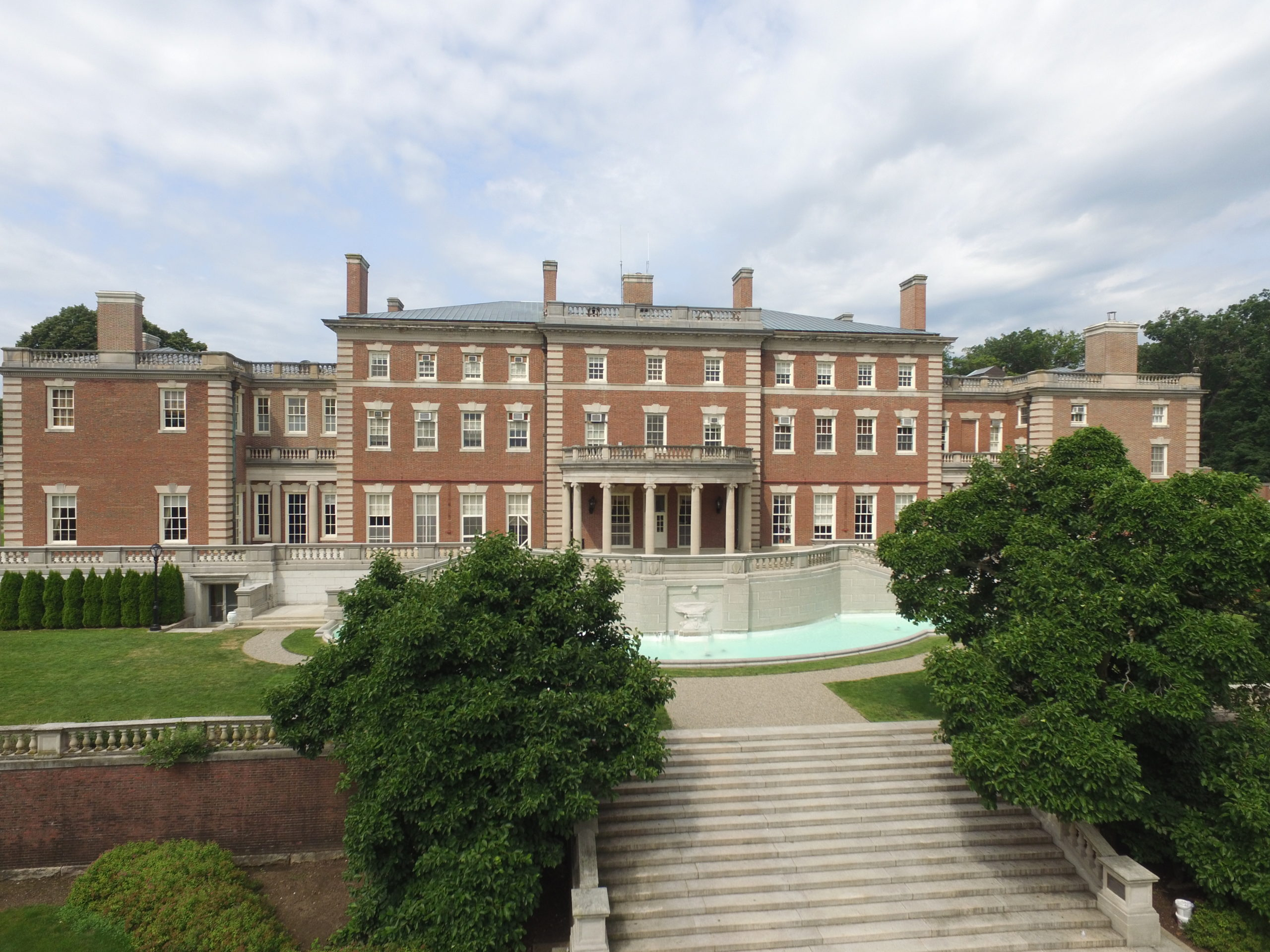 Hennessy Hall seen from behind, with a fountain and garden before it.
