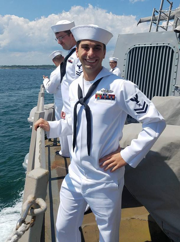 Dillon Pontes, a naval officer, stands on the deck of a ship in his uniform, with his right hand resting on the railing overlooking the ocean. Another sailor stands behind him.