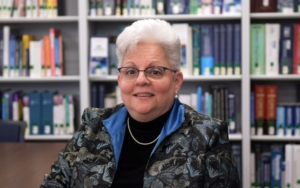 Middle-aged woman sits in front of a bookshelf and smiles.