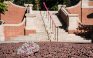 """In the foreground, there are words reading """"love yourself"""" written on a gray rock. The rock is resting on gravel and outside stairs snake up behind this area on the Florham Campus."""
