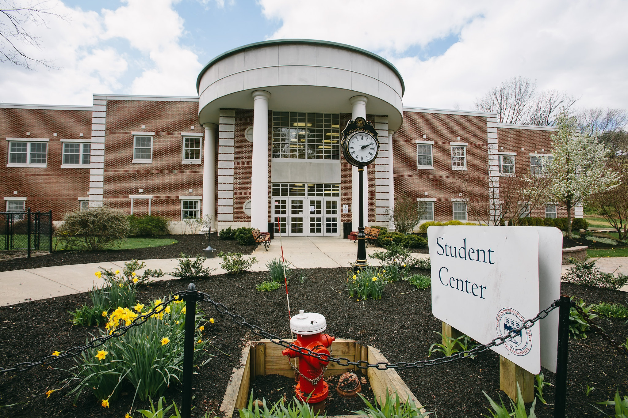 "A building with a clock tower and sign in front of it reading ""Student Center""."