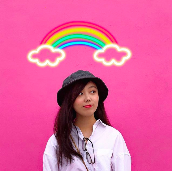 A young woman stands in front of a bright pink wall, with a rainbow above.