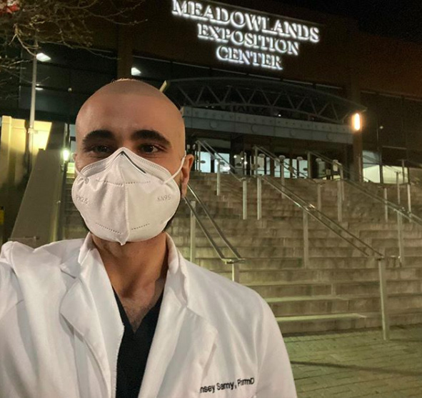 A male pharmacist wearing a mask stands outside of a temporary hospital built at the Meadowlands Exposition Center.