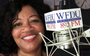 A woman sits behind a WFDU microphone.