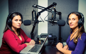 In studio, two women sit ready to record a podcast.
