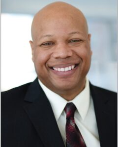 A professional headshot of a man wearing a suit