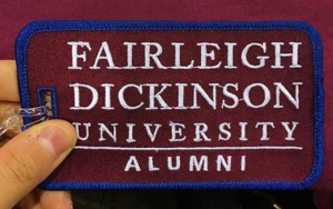 An alumni luggage tag in the FDU colors