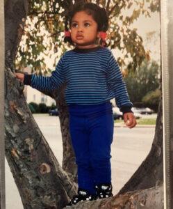 Tiffanie Arokiaswamy as a small child climbing in a tree.