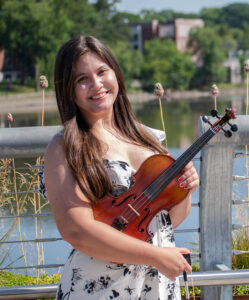 Cassandra Laman poses with her violin in front of the Hackensack River after performing at the Metropolitan Campus.