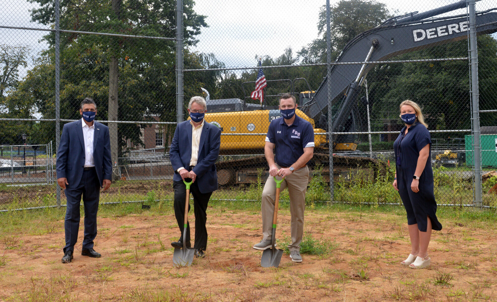 President Capuano, Vice President for Facilities & Auxiliary Services Dick Frick, Head Baseball Coach Jamie Quinn and Director of Athletics Jenn Noon stand on the location of the future Naimoli Field. Frick and Quinn hold shovels.