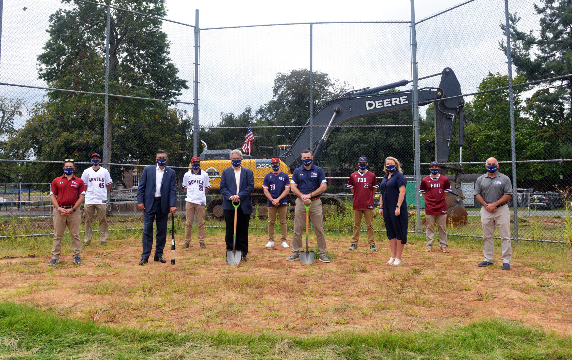 Members of the FDU Devils baseball team join University President Capuano, VP for Facilities & Auxiliary Services Dick Frick, head baseball coach Jamie Quinn, Director of Athletics Jenn Noon at the Naimoli Field groundbreaking at FDU's Florham Campus. Capuano holds a bat, Frick and Quinn hold shovels.