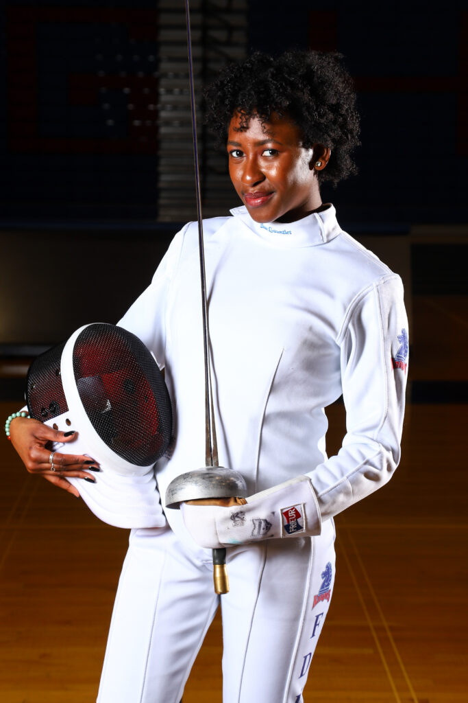 A portrait of Natalia Toby in her fencing gear with her epee sword.