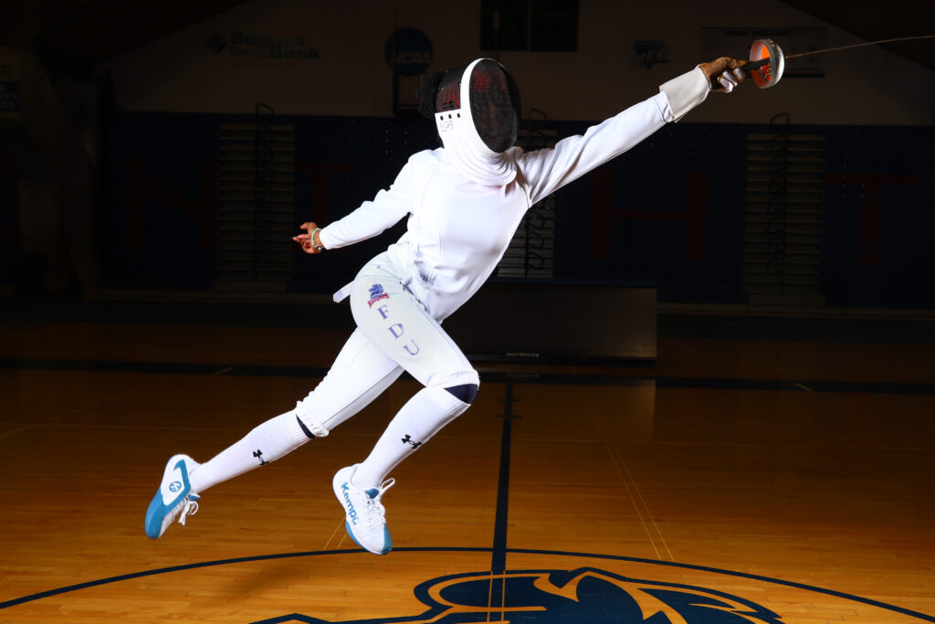 Natalia Toby in an action pose wearing her fencing uniform and using her epee sword.