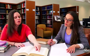 Two female professors review notes at a table in the library.