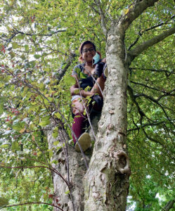 Tiffanie as young adult climbing in a tree.