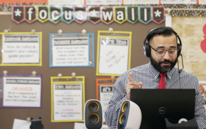 A male teacher wears headphones and works at his laptop in a classroom.